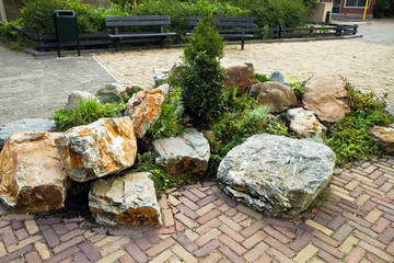 Decorative rock-garden in city street with benches