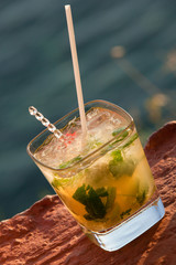 Mojito  cocktail .Cocktail against sea during sunset lights
