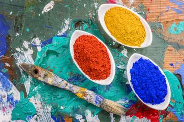 Bunte Farbpigmente in Porzellanschälchen auf einer Holzpalette