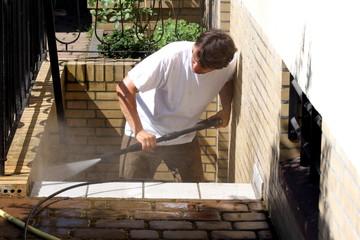 Mann reinigt Treppe mit Hochdruck