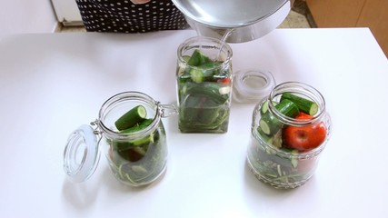 Adding hot brine to jars with vegetables