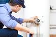 Leinwanddruck Bild - Plumber repairing an hot-water heater