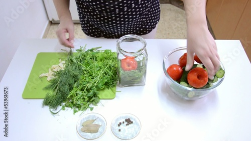 Placing cucumbers, tomatoes into jar