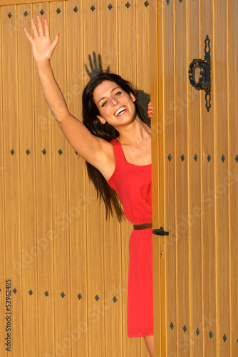Woman waving at house entrance