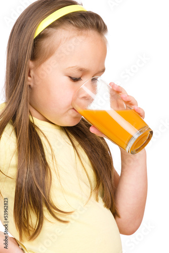 Little girl is drinking orange juice
