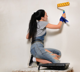 Young woman painting with a roller