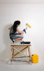 Young girl painting while redecorating