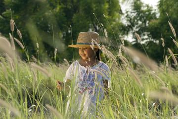 Linda niña campestre caminando a través del pasto