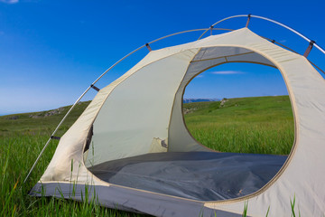 white touristic tent on a green grass