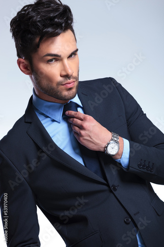 business man fixes his tie