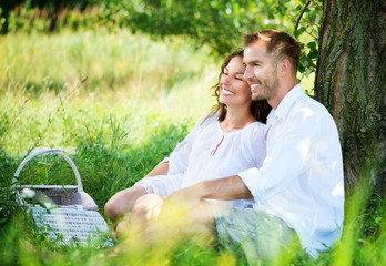 Young Couple Having Picnic in a Park. Happy Family Outdoor