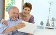 Best Ager Seniorenpaar 60+ freut sich mit Tablet