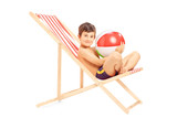 Boy with a beach ball sitting on an outdoor chair