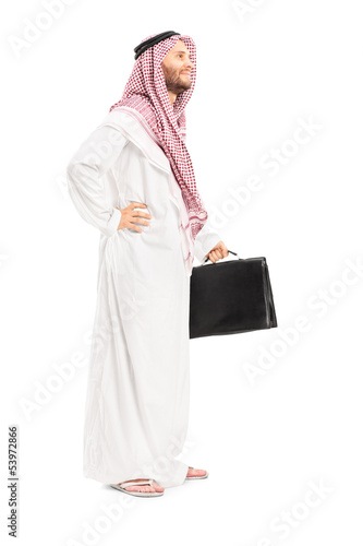Full length portrait of a male arab person with suitcase posing
