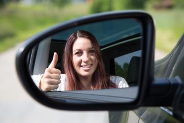 Autofahrerin zeigt Daumen hoch im Spiegel