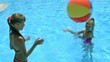 Children playing beach ball in swimming pool.