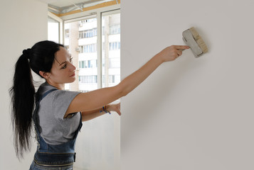 Attractive woman painting a house wall