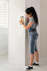 Woman resurfacing a wall