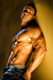 Handsome young bodybuilder against wall