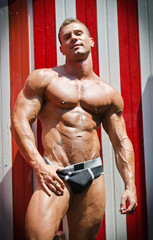 Attractive young bodybuilder against striped beach changing room