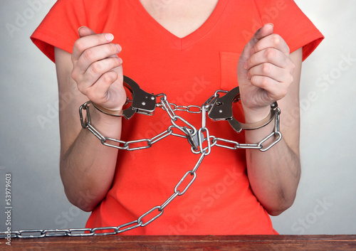 Prisoner in handcuffs on grey background