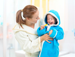 Dental hygiene in bathroom. Mother and child cleaning teeth toge