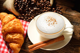 A cup of cappuccino with coffee beans and croissant