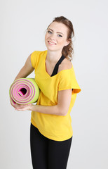 Portrait of beautiful young woman with gym mat