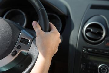 Hand am Lenkrad eines Autos