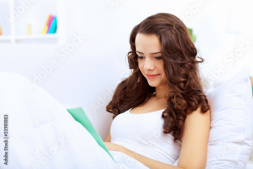 Young woman at home with a book