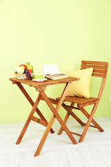 Wooden table with fruit,book and cup on it in room