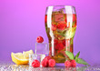 Iced tea with raspberries and mint on purple background