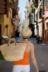 frau mit einkaufskorb geht durch mediterrane stadt
