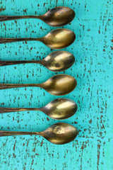 Vintage metal spoons on wooden table close-up