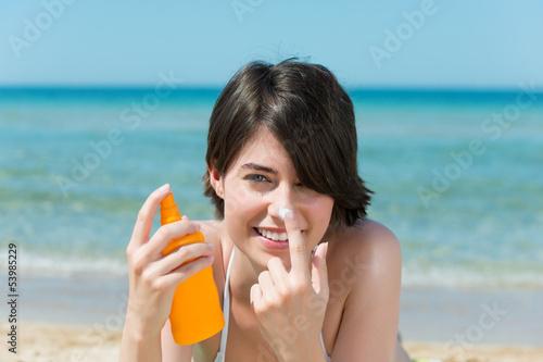 frau am strand cremt sich das gesicht mit sonnencreme ein