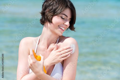 lächelnde frau am meer cremt sich ein