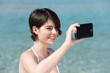 frau am meer fotografiert mit ihrem smartphone