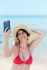 lachende frau fotografiert sich selbst am strand