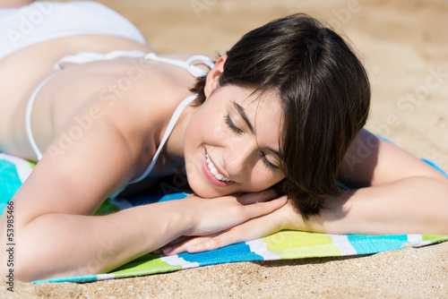 junge frau liegt am strand und genießt die sonne