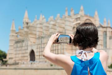 frau fotografiert eine kirche mit ihrem handy