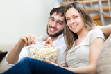 Young couple eating pop-corn on the sofa