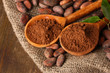 Cocoa powder in spoons and cocoa beans on wooden background