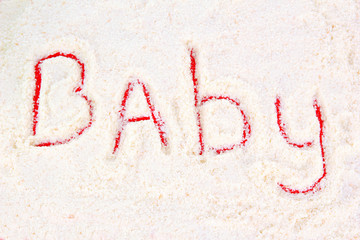 Word baby making with powdered milk on red background