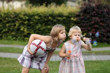 Dwie siostry z piłką dmuchają bańki mydlane.