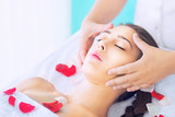 Young beautiful woman receiving head massage at spa