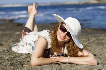 deniz kenarında uzanan güneş gözlüklü ve şapkalı bayan model