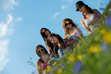 group of girls sitting on grass and having fun