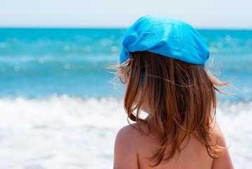 Bambina al mare con copricapo azzurro