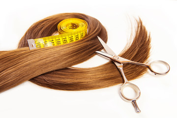 hairdresser scissors on hair with measuring tape