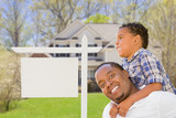 Father and Son In Front of Blank Real Estate Sign and House